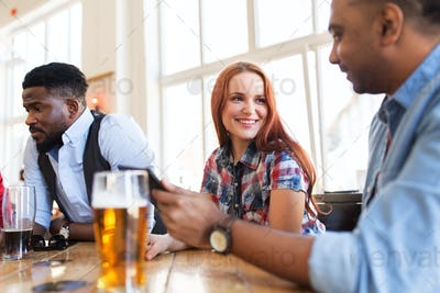 happy friends with tablet pc drinking beer at bar