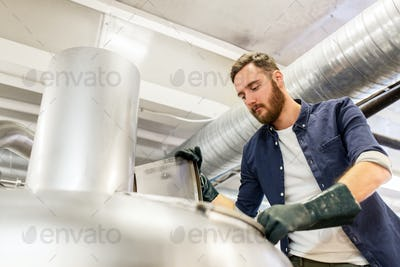 man working at craft brewery or beer plant