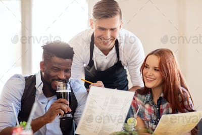 waiter and couple with menu and drinks at bar