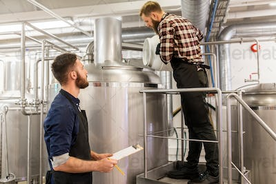 men working at craft brewery or beer plant