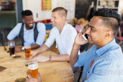 man calling on smartphone and drinking beer at bar