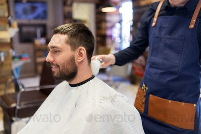 barber with brush cleaning male neck at barbershop