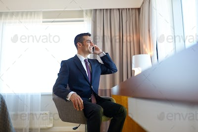 businessman calling on smartphone at hotel room