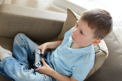 little boy with gamepad playing video game at home