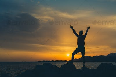 Girl hiker with arms outstretched enjoy beach and sea