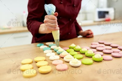 chef with injector squeezing filling to macarons