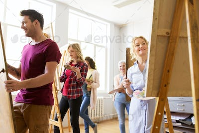 artists with brushes painting at art school