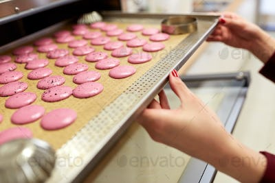 chef with macarons on oven tray at confectionery