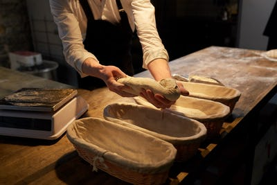 baker with dough rising in baskets at bakery