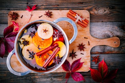 Hot mulled cider drink with citrus, apples, cinnamon sticks, cloves and anise in cooking pan