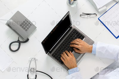 doctor hands typing on laptop at clinic
