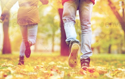 young couple running in autumn park