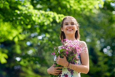 happy young woman with flowers in summer park