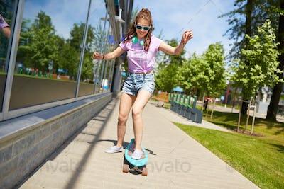 happy teenage girl in shades riding on longboard