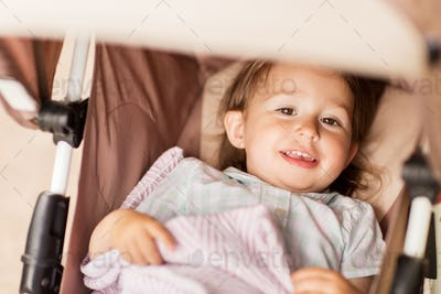 little child or baby lying in stroller outdoors