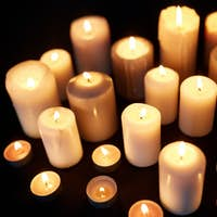 candles burning in darkness over black background