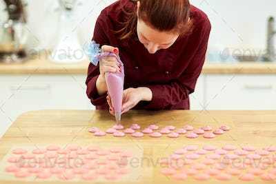 chef with injector squeezing macaron batter