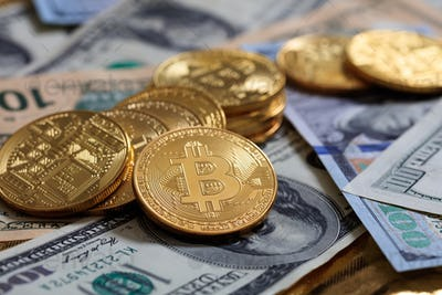 Bitcoins stack on dollar banknotes background