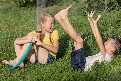 Happy kids sitting on the grass and pouring water from a hose.