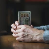 Man's hand holding a dollar bill