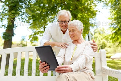 happy senior couple with tablet pc in city park