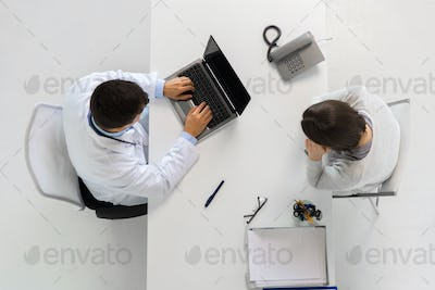 doctor with laptop and woman patient at hospital