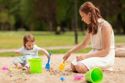 happy mother and baby girl playing in sandbox