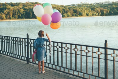 Cheerful girl holding colorful balloons and childish suitcase en