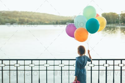 Cheerful girl holding colorful balloons and childish suitcase  l