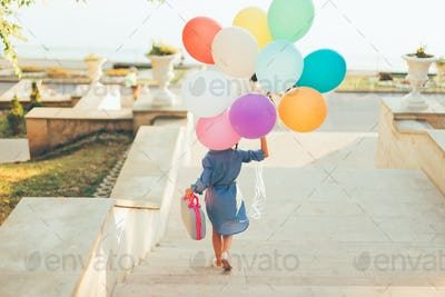 Girl running on the stairs holding colorful balloons and childis