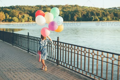 Cheerful girl holding colorful balloons and childish suitcase wa