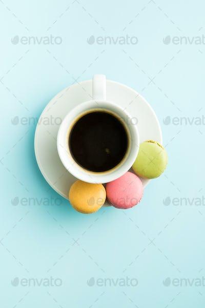 Tasty sweet macarons and coffee cup.