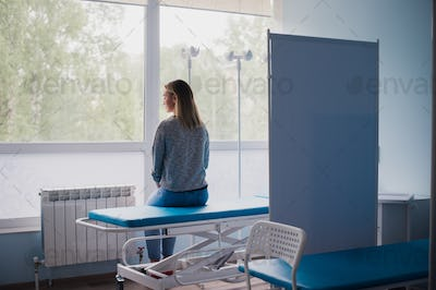 Young pregnant woman sitting on bed in comfortable ward, waiting for doctor thoughtfully