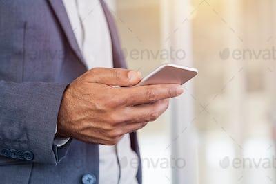 Businessman hand holding smartphone