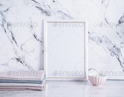 Blank frame and stack of fabrics over marble table