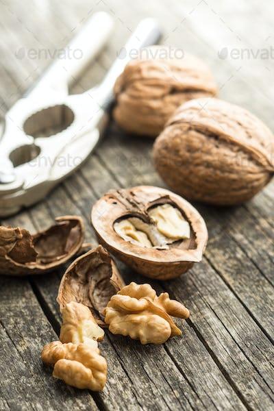 Cracked dried walnuts and nutcracker.