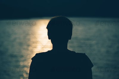 Silhouette of depressed sad woman standing by the lake