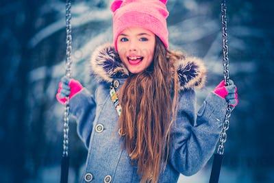 Charming little girl on swing in snowy winter