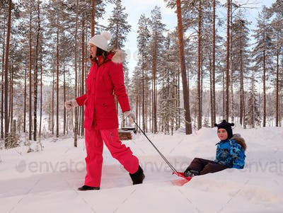 Little boy with her mother in a snow landscape