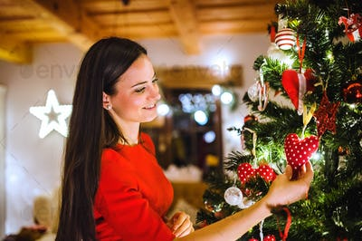 Young woman in front of Christmas tree decorating it