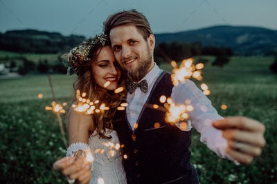 Beautiful bride and groom on a meadow in the evening.