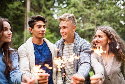 Beautiful teenagers in forest with sparklers.