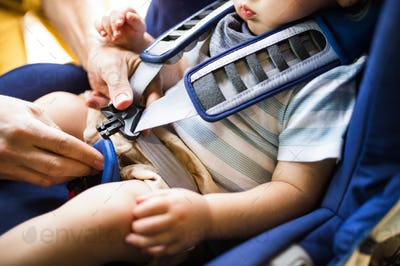 Father fastening seat belt for his son sitting in the car.