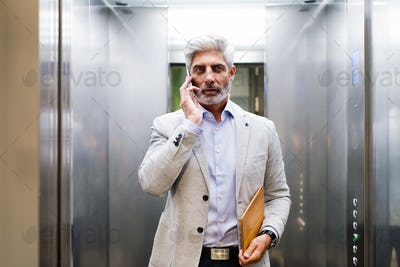 Mature businessman with smartphone in the elevator.