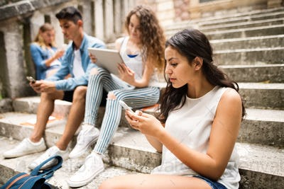 Teenagers with smartphones and tablets on stone steps.