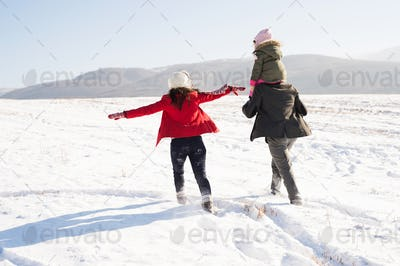Father and mother with their daughter on a walk, winter nature.
