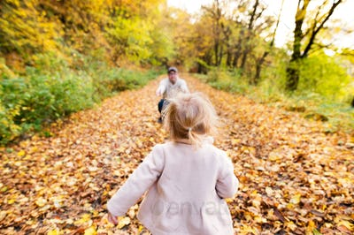 Little girl running to her father. Colorful autumn forest.