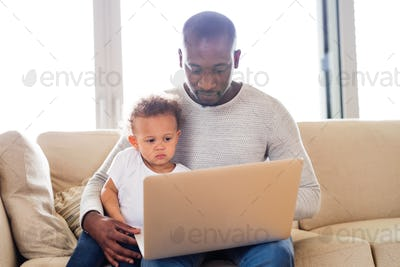 Afro-american father with little daughter at home holding laptop