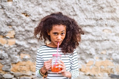Beautiful african american girl drinking juice, old concrete wal
