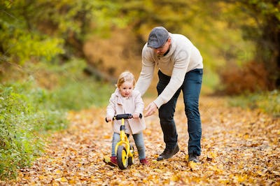 Father with little daughter cycling in autumn park.